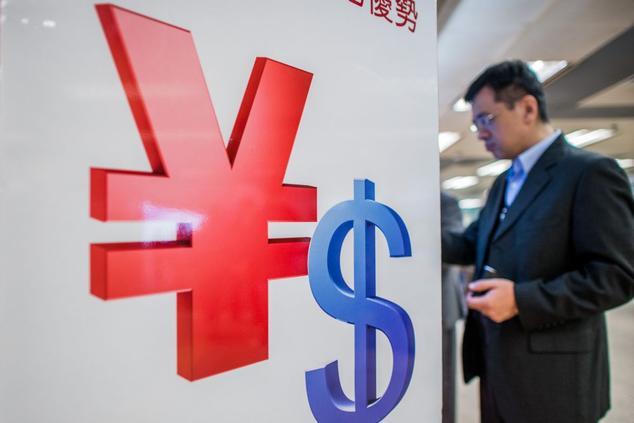 Китайские граждане официально за год могут обменять на иностранную валюту сумму, не превышающую 50 000 долларов США. Фото: PHILIPPE LOPEZ/AFP/Getty Images