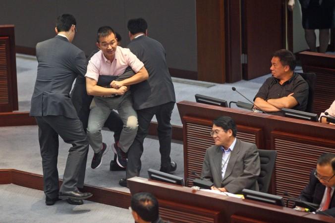 Члена Законодательного совета Рэймонда Чхань Чхи-Чхуэна (Raymond Chan Chi-chuen) выносят охранники после его протеста. Он посчитал, что правительство нечестно выразило позицию народа о гражданском кандидате, 15 июля 2014 года, Гонконг. Фото: Epoch Times