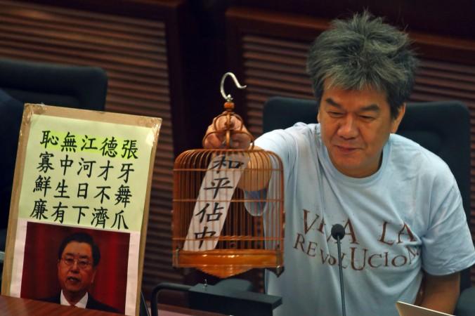 Законодатель Лён Кхуок-хун держит птичью клетку, в которой на листке написано: «Конституционная реформа», 21 июля, Гонконг. Фото: Epoch Times