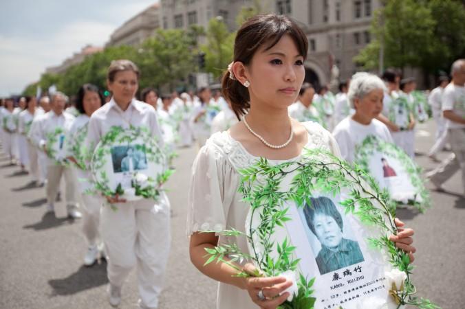 Последователи Фалуньгун несут фотографии жертв преследований, 18 июля 2011 года. Фото: Epoch Times
