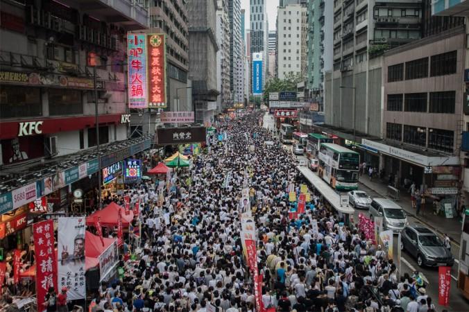 Демонстранты маршируют в поддержку демократии в Гонконге 1 июля 2014 года. В этот день в Гонконге традиционно проходят протесты. Он также знаменует годовщину передачи бывшей британской колонии Китаю в 1997 году с условием соблюдения принципа «одна страна, две системы». Фото: Philippe Lopez/AFP/Getty Images