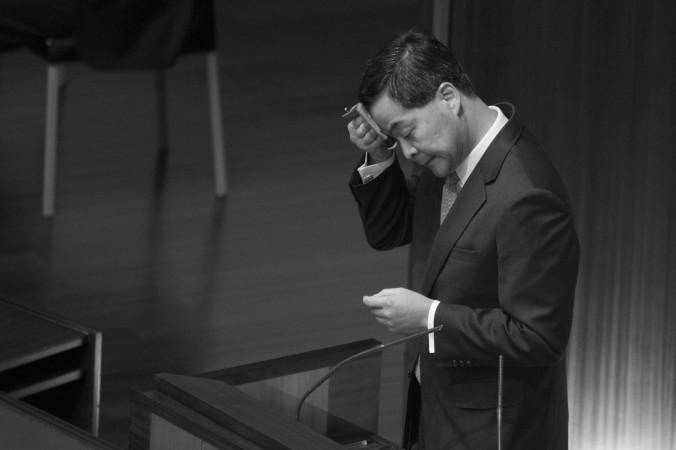 Глава Гонконга Лян Чжэньин вытирает лоб во время выступления в Законодательном совете Гонконга 16 января 2013. Фото: Jerome Favre/Getty Images