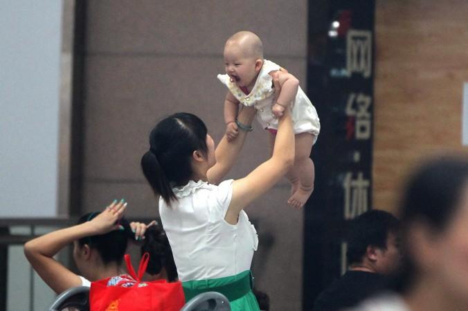 Женщина держит ребёнка, Чжэнчжоу, Хэнань, 29 июля 2014 года. Недавно государственные СМИ Китая сообщили из сверхприбылях за счёт эксплуатации суррогатных матерей и селективных абортов, которые сопровождают этот бизнес. Фото: STR/AFP/Getty Images