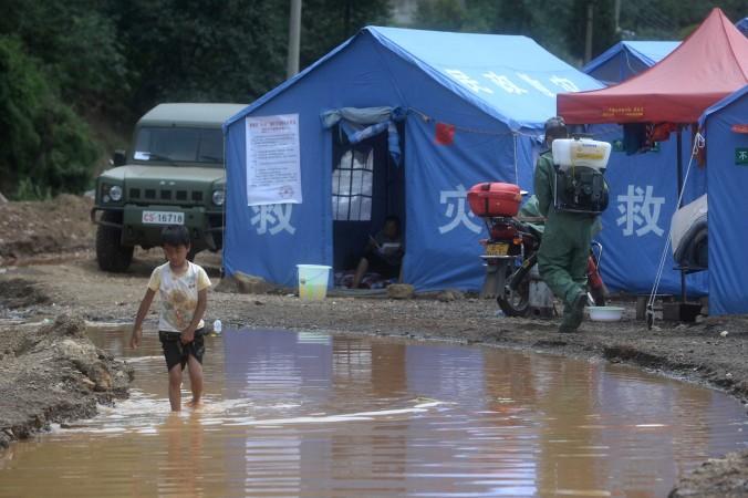 Мальчик пробирается через затопление рядом с временным убежищем в посёлке Лунтоушань провинции Юньнань 7 августа 2014 года. Местные чиновники зарабатывают на горе, продавая пострадавшим бутилированную воду и продукты питания, собранные волонтёрами. Фото: AFP/Getty Images