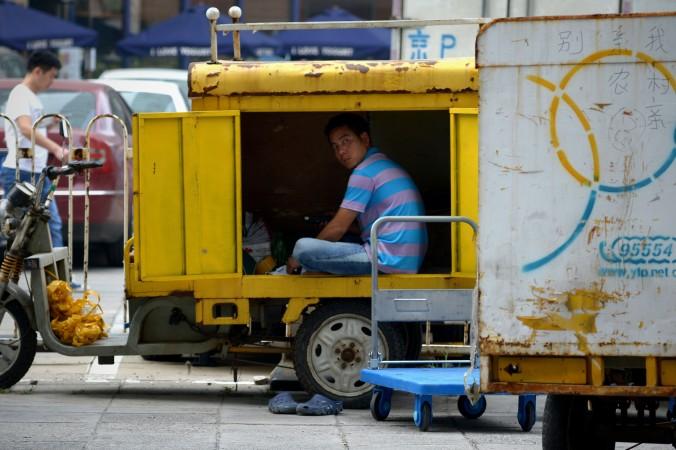 Курьерская доставка на трёхколёсном транспорте, Пекин, 18 августа 2014 года. Прямые иностранные инвестиции в Китай упали до двухлетнего минимума, согласно данным правительства от 18 августа. Фото: Wang Zhao/AFP/Getty Images