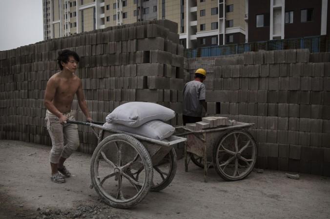 Китайский строитель толкает тачку с цементом на строительной площадке нового жилого комплекса в Пекине 29 августа 2014 года. Фото: Kevin Frayer/Getty Images