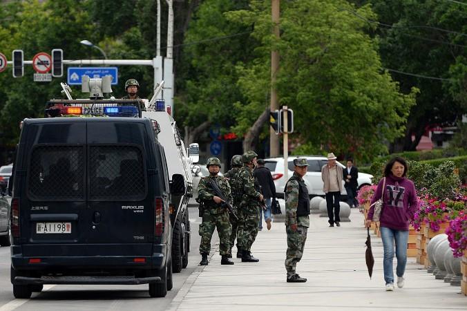 Вооружённая китайская полиция патрулирует улицы в Урумчи, столице Синьцзян-Уйгурского автономного района, 23 мая 2014 года. Возможно, тысячи человек погибли в Кашгаре в последний день священного для мусульман месяца. Фото: Goh Chai Hin/AFP/Getty Images