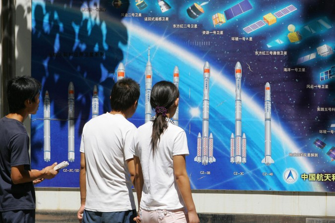 Люди рассматривают плакат с изображением ракет и космической программы Китая, 29 августа 2007 года, парк Пекина. Китайский режим недавно создал «патентного тролля» и получил ещё один доступ к технологиям. Для этого режим также использует кибершпионаж. Фото: Frederic J. Brown/AFP/Getty Images