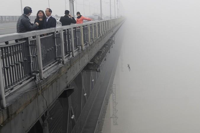 Парень падает в реку Янцзы с моста в Ухане 27 февраля 2013 года. За несколько минут до этого другой человек покончил жизнь самоубийством таким же образом. Фото: STR/AFP/Getty Images
