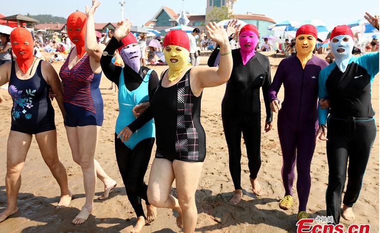 Женщины в закрытых купальниках и масках в Национальный День фитнеса на пляже в Циндао, провинция Шаньдун, 8 августа 2014 года. Азиатки любят, чтобы их кожа была белой. Фото: China News Service/Xu Chongde