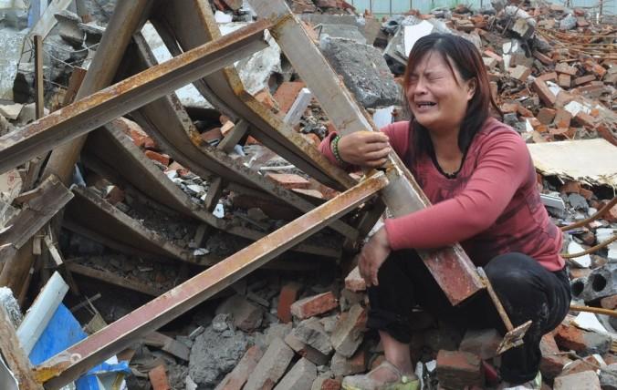 Жена Чжан Хунвэя рыдает среди обломков своего дома в городе Синьчжэн провинции Хэнань 8 августа 2014 года. Г-н Чжан и его жена были похищены группой неизвестных, которые схватили их ночью, во время сна. Когда супругов несколько часов спустя отпустили, их дом был уже снесён. Фото: скриншот/163.com