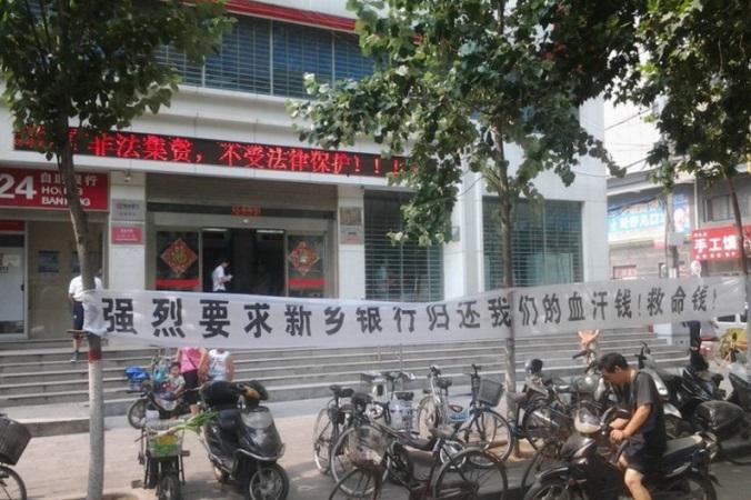 Обманутые вкладчики натянули баннер у банка Синьсяна в провинции Хэнань, август 2014 года. Чжан Ли, глава отделения банка, заимствовал огромные суммы у вкладчиков и покончил жизнь самоубийством, когда не смог платить проценты. Фото: скриншот/Tianya.cn