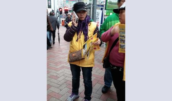 Нг Мань-тин (в жёлтой куртке), член Ассоциации содействия молодёжи Гонконга, под видом последовательницы Фалуньгун раздаёт в Гонконге литературу с клеветой на Фалуньгун. Недавно суд приговорил её к 12 суткам ареста. Фото: Epoch Times