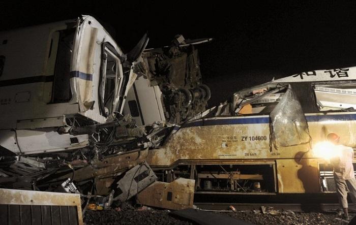 Спасатель работает на месте крушения скоростного поезда 23 июля 2011 года в китайской провинции Чжэцзян. Обломки поезда D301 были спешно зарыты в земле, но потом, в связи с сильным общественным осуждением, чиновники были вынуждены выкопать их снова для проведения расследования. Фото: AFP/Getty Images