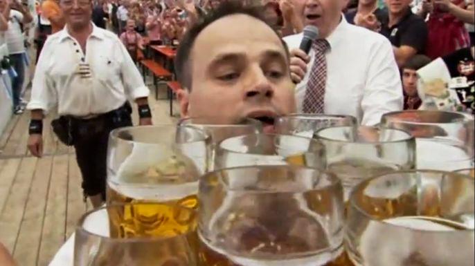 В Германии мужчина пронес 27 литровых пивных кружек одновременно. Скриншот видео.