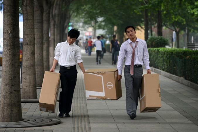 Два китайских парня несут коробки по улице в Пекине 25 июня 2013 года. Пекинский университет опубликовал обзор, согласно которому средняя стартовая зарплата выпускников вузов в 2014 году составила только 2400 юаней ($400), а 40% выпускников полагаются на финансовую поддержку своих родителей. Фото: Wang Zhao/AFP/Getty Images