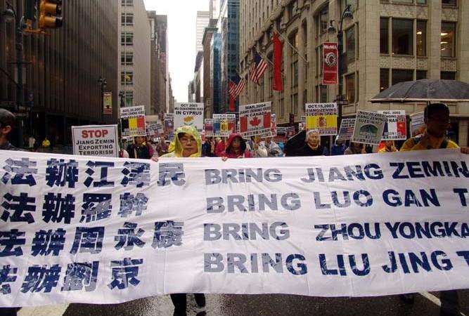 На параде в Нью-Йорке последователи Фалуньгун несут транспарант с призывом привлечь к ответственности четырёх чиновников китайского режима за их роль в кампании преследования духовного учения Фалуньгун, 20 ноября 2004 года. Как глава аппарата безопасности, Чжоу Юнкан играл ведущую роль в репрессиях Фалуньгун. Фото: en.minghui.net