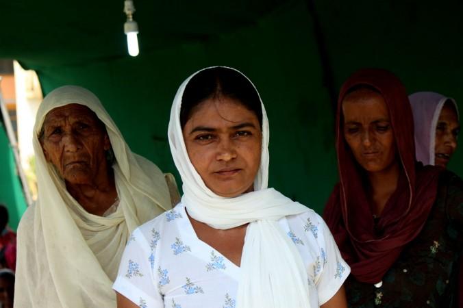 Вдова, у которой несколько месяцев назад умер муж, стоит у лагеря беженцев около средней школы в Даблехаре, штат Джамму, 28 августа 2014 г. Фото: Venus Upadhayaya/EpochTimes