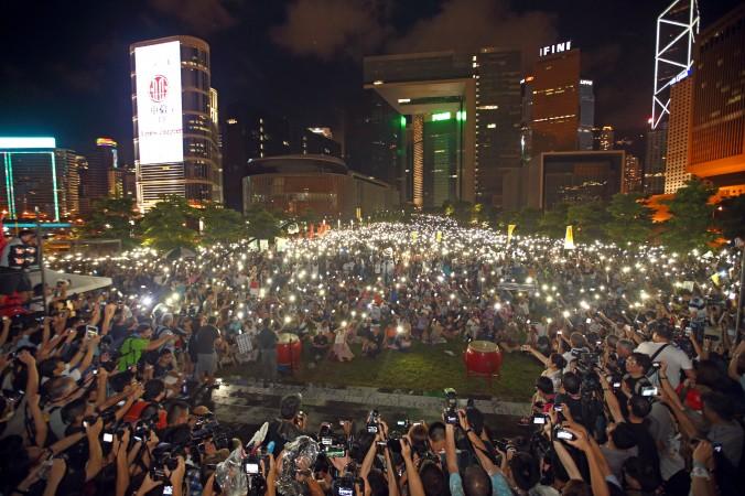 Митинг возле правительственных учреждений Гонконга 31 августа 2014 года в знак протеста против решения Пекина продолжать ограничивать демократию в Гонконге. Протестующие включили мобильные телефоны как свечи, чтобы выразить гражданское неповиновение. Фото: Poon/Epoch Times