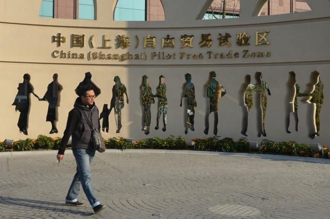 Китаец проходит мимо сооружения с надписью «Шанхайская пилотная зона свободной торговли» 28 ноября 2013 года. Китайские власти недавно заявили, что позволят в иностранным кампаниям создавать больницы в семи городах и провинциях. Фото: Peter Parks/AFP/Getty Images
