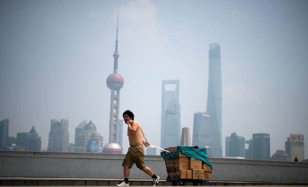 Китаец тащит тележку с товаром, 25 августа 2014 года, Шанхай. В Китае огромный разрыв между богатыми и бедными. Однако негибкая политическая система мешает реформам. Фото: JOHANNES EISELE/AFP/Getty Images