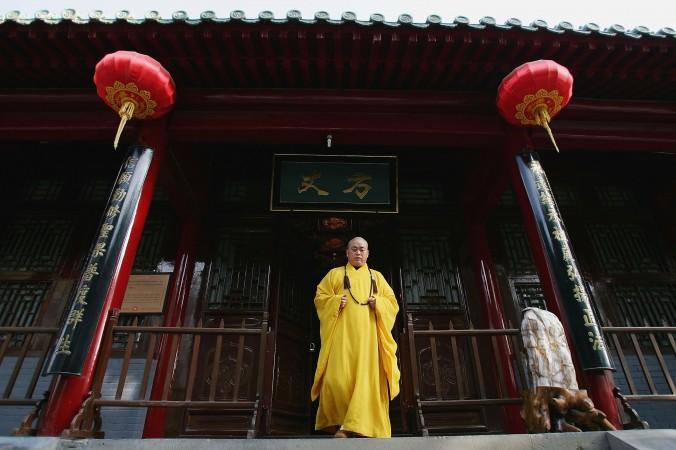 Ши Юнсинь, настоятель монастыря Шаолинь, выходит из храма 7 апреля 2005 года, город Дэнфэн, провинция Хэнань. Храм хочет отсудить у местных властей долю от доходов за туризм. Фото: Cancan Chu/Getty Images