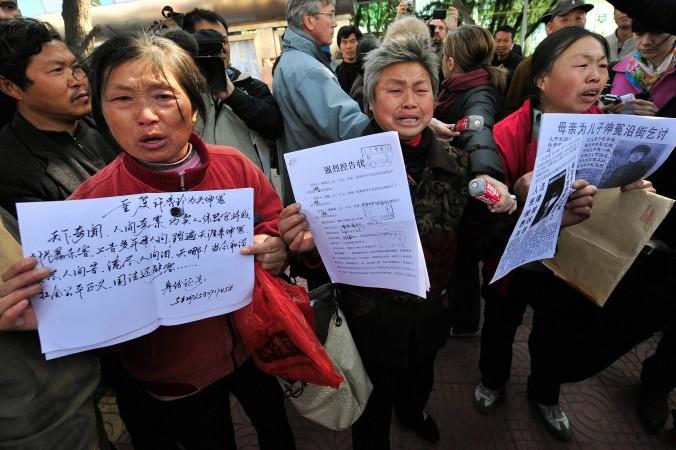 Петиционеры в Пекине показывают документы, подтверждающие, что с ними обошлись несправедливо. Недавно в Синьцзяне местные жители ворвалась в «чёрную тюрьму», чтобы спасти петиционера, незаконно задержанного службой безопасности. Фото: Teh Eng Koon/AFP/Getty Images