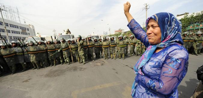 Китайские спецназовцы смотрят на протестующую мусульманку в Урумчи, столице Синьцзян-Уйгурского автономного района, 7 июля 2009 года. 21 сентября 2014 года взрывы в Синьцзяне унесли жизни двух человек. Фото: Peter Parks/AFP/Getty Images