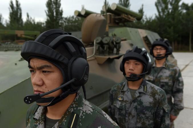 Курсанты Народно-освободительной армии Китая ждут приказа возле самоходки Т-89, 22 июля 2014 года, Пекин. Лидер Китая Си Цзиньпин призывал к развитию технологий информационных войн. Фото: GREG BAKER/AFP/Getty Images
