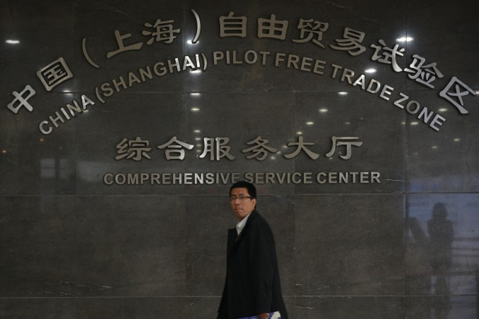Прохожий проходит возле сервисного центра Шанхайской зоны свободной торговли 28 ноября 2013 года. Руководитель проекта недавно был обвинён в коррупции. Фото: Peter Parks/AFP/Getty Images