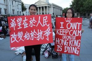Гонконцы за рубежом собрались на Трафальгарской площади в центре Лондона 1 июля 2014 года, чтобы поддержать марш протеста в Гонконге. Две молодые дамы держат плакаты: «Люди надеются на изменения после протеста» (слева); «Я не могу молчать, потому что Гонконг умирает» (справа). Фото: Li Jingheng/Epoch Times