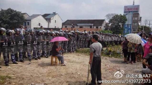 Крестьяне протестуют против строительства магазина на отобранной у них земле. Посёлок Бали провинции Чжэцзян. Август 2014 года. Фото с epochtimes.com