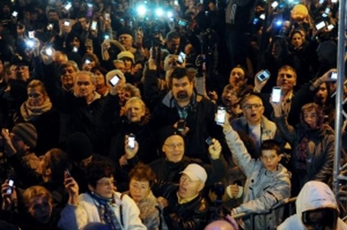Венгерские граждане подняли свои мобильные телефоны в знак протеста против правительственного нового налога на интернет, Будапешт, Венгрия, 26 октября 2014 года. Фото: ATTILA KISBENEDEK / AFP / Getty Images
