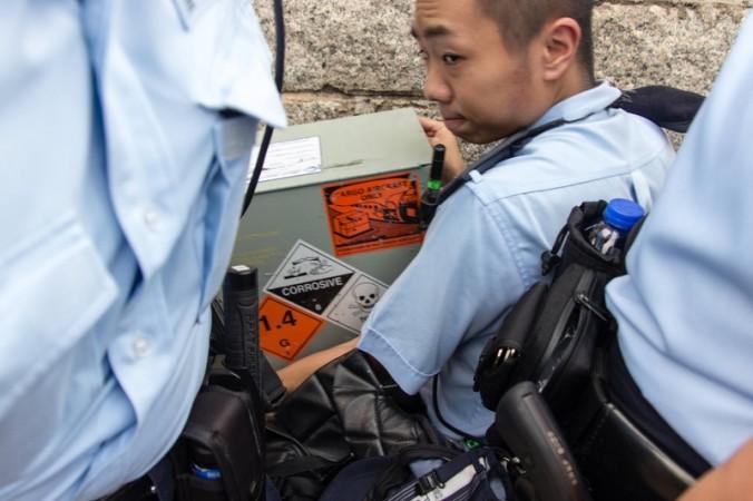 Полицейский несёт в офис главы Гонконга коробку со знаками, предупреждающими об опасности. Фото: Leung Kwok-hung Facebook