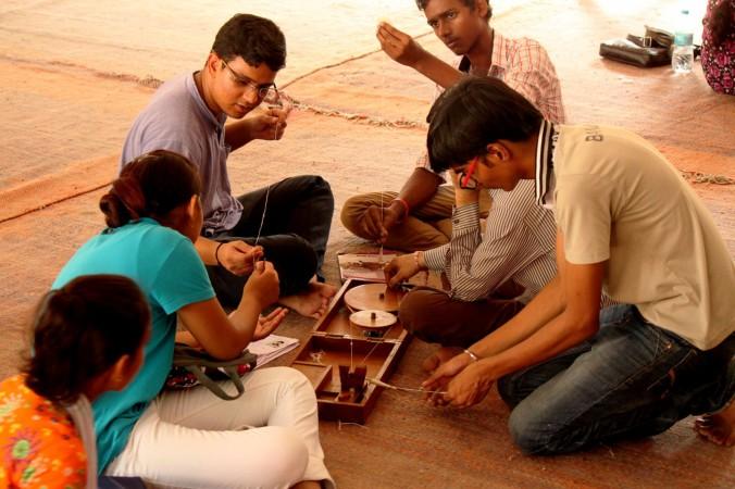 Группа студентов работает с прялкой в Центре Ганди Бхаван при Университете Дели 18 сентября 2014 г. Цель этого курса ― познакомить индийскую молодёжь с идеалами Ганди. Фото: Venus Upadhayaya/Epoch Times