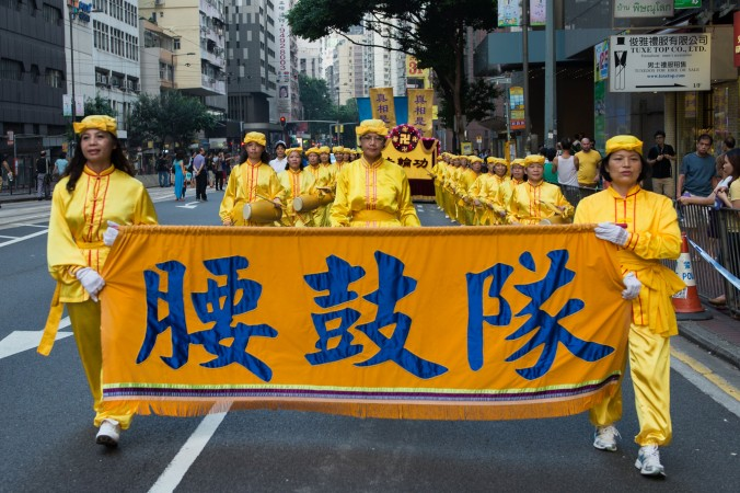 В День образования КНР 1 октября 2014 года последователи Фалуньгун вместе с представителями глобального центра по выходу из компартии Китая провели марш в Гонконге. Фото: Benjamin Chasteen/Epoch Times