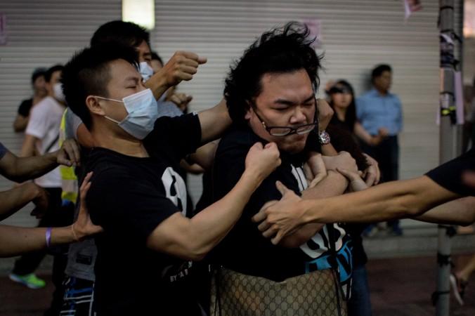 Группа хулиганов в масках избивает мужчину, который пытался помешать им разобрать баррикады протестующих в гонконгском районе Козуэй-Бей 3 октября 2014 года. Источники говорят, что глава Гонконга Лян Чжэньин нанял мафиозные группировки, чтобы преследовать демонстрантов. Фото: Alex Ogle/AFP/Getty Images