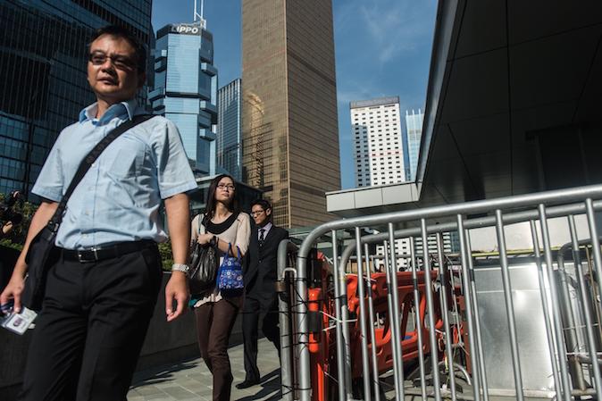 Государственные служащие проходят мимо баррикад демократических протестующих возле здания правительства. Фото: Anthony Wallace/AFP/Getty Images