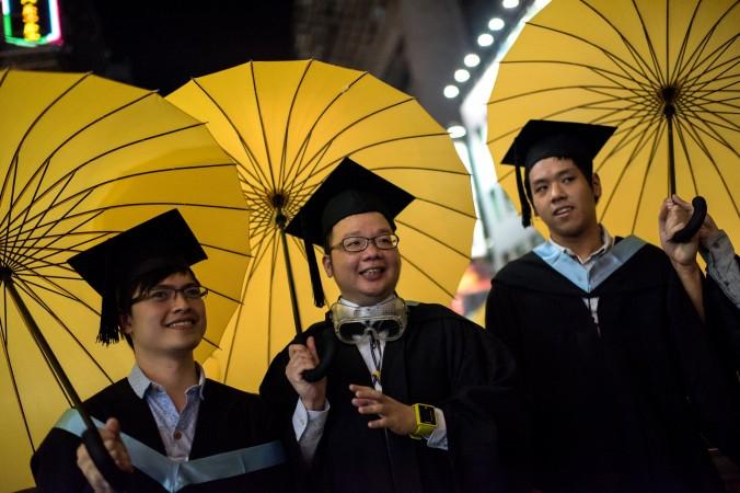 Студенты в выпускном наряде держат жёлтые зонты — символ движения за демократию в Гонконге, 19 октября 2014 года. Десятки студентов пришли с зонтами на церемонию вручения дипломов в Университет Линнань, чтобы выразить поддержку протестующим в Гонконге. Фото: Alex Ogle/AFP/Getty Images