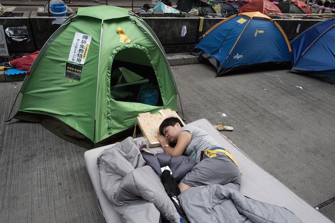 Протестующий спит на улице в гонконгском районе Монгкок 28 октября 2014 года. После месяца протестов движение «Оккупируй Централ» теряет динамику. Однако жители говорят, что оно уже изменило город навсегда. Фото: Nicolas Asfouri/AFP/Getty Images