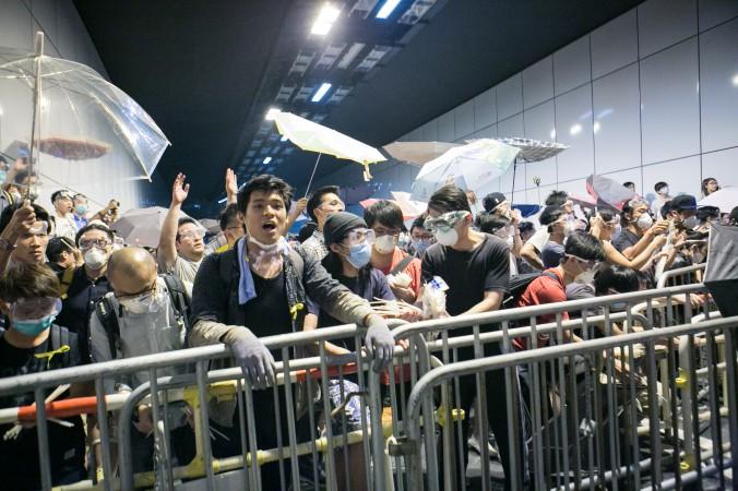 Продемократические протестующие в Гонконге в ночь на 15 октября пытались заблокировать Lung Wo Road, одно из главных шоссе в Гонконге, после того, как 14 октября полиция разобрала их баррикады. Фото: Benjamin Chasteen/Epoch Times