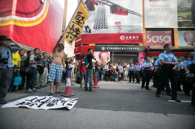 Полиция и демократические протестующие стоят друг против друга на улице Nathan Road после того, как полицейские рано утром разобрали все баррикады на Argyle Road в районе Монгкок, Гонконг, 17 октября 2014 года. Фото: Benjamin Chasteen/Epoch Times