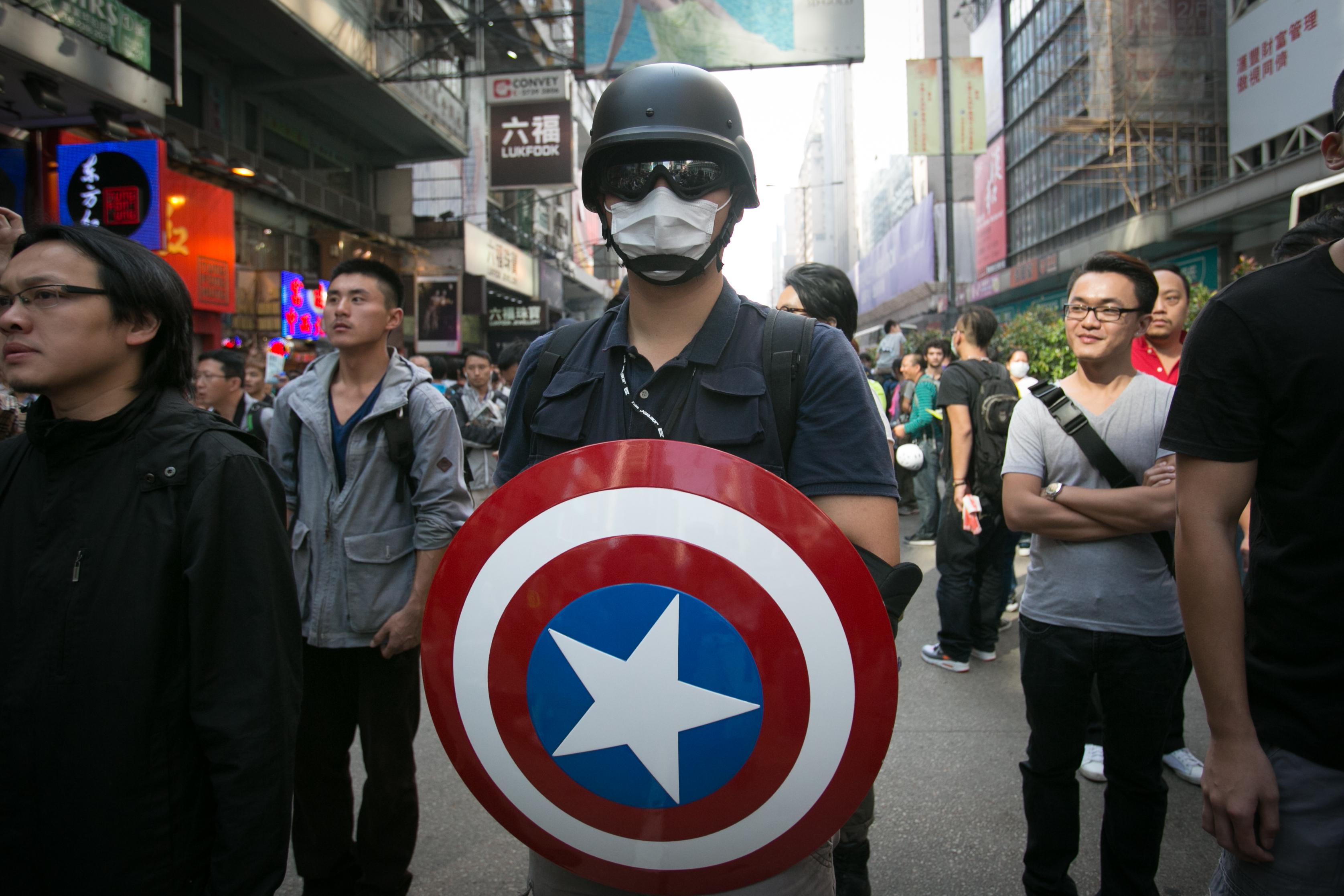 Демократический активист держит щит «Капитана Америки» через несколько часов после того, как полиция Гонконга убрала все баррикады в районе Монгкок 17 октября 2014 года. Фото: Benjamin Chasteen/Epoch Times