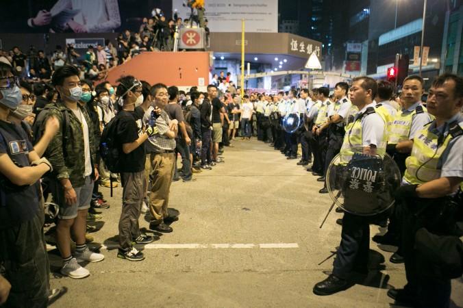Продемократические протестующие стоят напротив полицейских после того, как они всю ночь пытались блокировать Argyle Street и Nathan Road в Монгкоке, Гонконг, 18 октября 2014 года. Фото: Benjamin Chasteen/Epoch Times