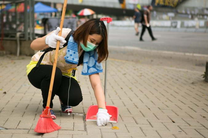 Волонтёр из протестующих тщательно вычищает мусор между брусчаткой на улице, которая ведёт к месту протестов в Центральном районе Гонконга, 9 октября 2014 года. Девушка сказала, что никто не просил её делать это, она просто решила, что кто-то должен убирать места протестов. Фото: Benjamin Chasteen/Epoch Times