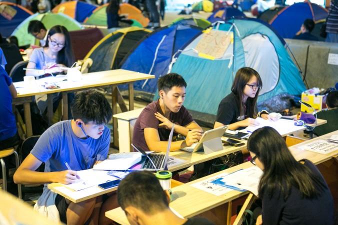 Студенты делают домашнюю работу на месте протестов в Центральном районе Гонконга 14 октября 2014 года. Им поставили генератор и обеспечили Wi-Fi. Фото: Benjamin Chasteen/Epoch Times