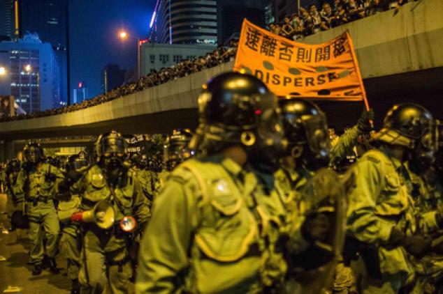 Спецподразделение полиции марширует в Гонконге 28 сентября. Силовики несут баннер со словами: «Быстро разойдитесь, иначе будет открыт огонь». Фото: Bill/EPOCH TIMES