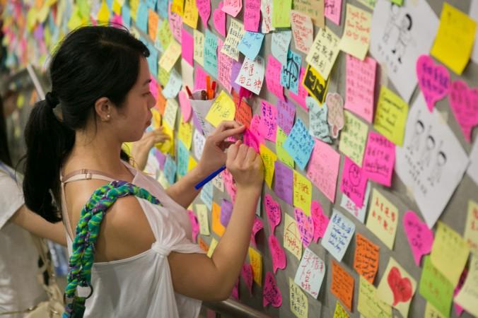 Женщина оставляет записку на стене здания в районе Гонконга Адмиралти 2 октября 2014 года. Фото: Benjamin Chasteen/Epoch Times