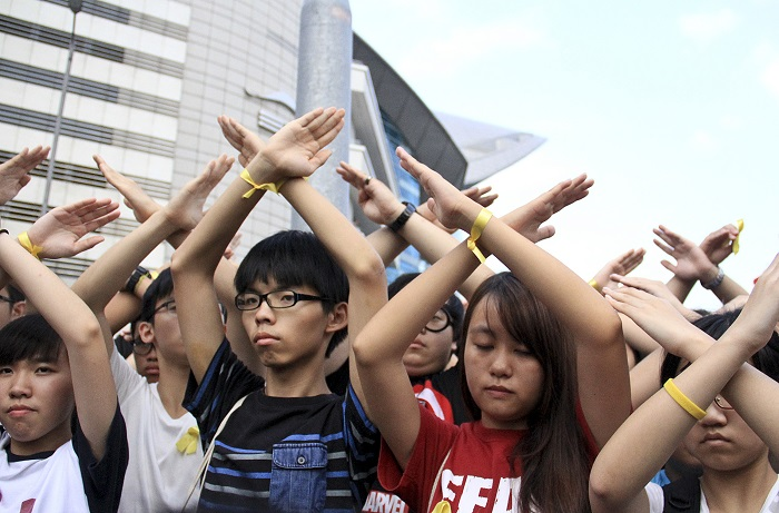 Студенты в знак протеста скрещивают руки во время церемонии поднятия флага на площади Цзиньцзыцзин в Гонконге 2 октября 2014 года. Они призывают главу Гонконга Лян Чжэньина уйти в отставку. Фото: Pu Huien/Epoch Times