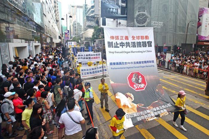 Во время шествия последователи Фалуньгун несут плакат с призывом остановить санкционированное коммунистическим режимом насильственное извлечение органов у их единомышленников в Китае. Гонконг. Июль 2014 года. Фото: minghui.org